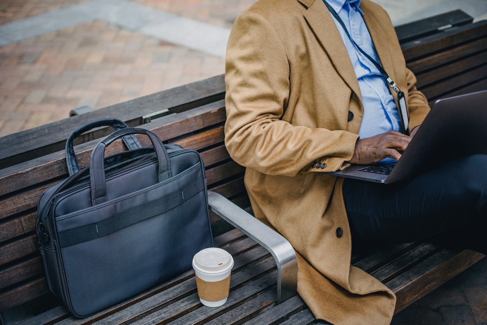 crop faceless man using a laptop on bench next to coffee and black briefcase