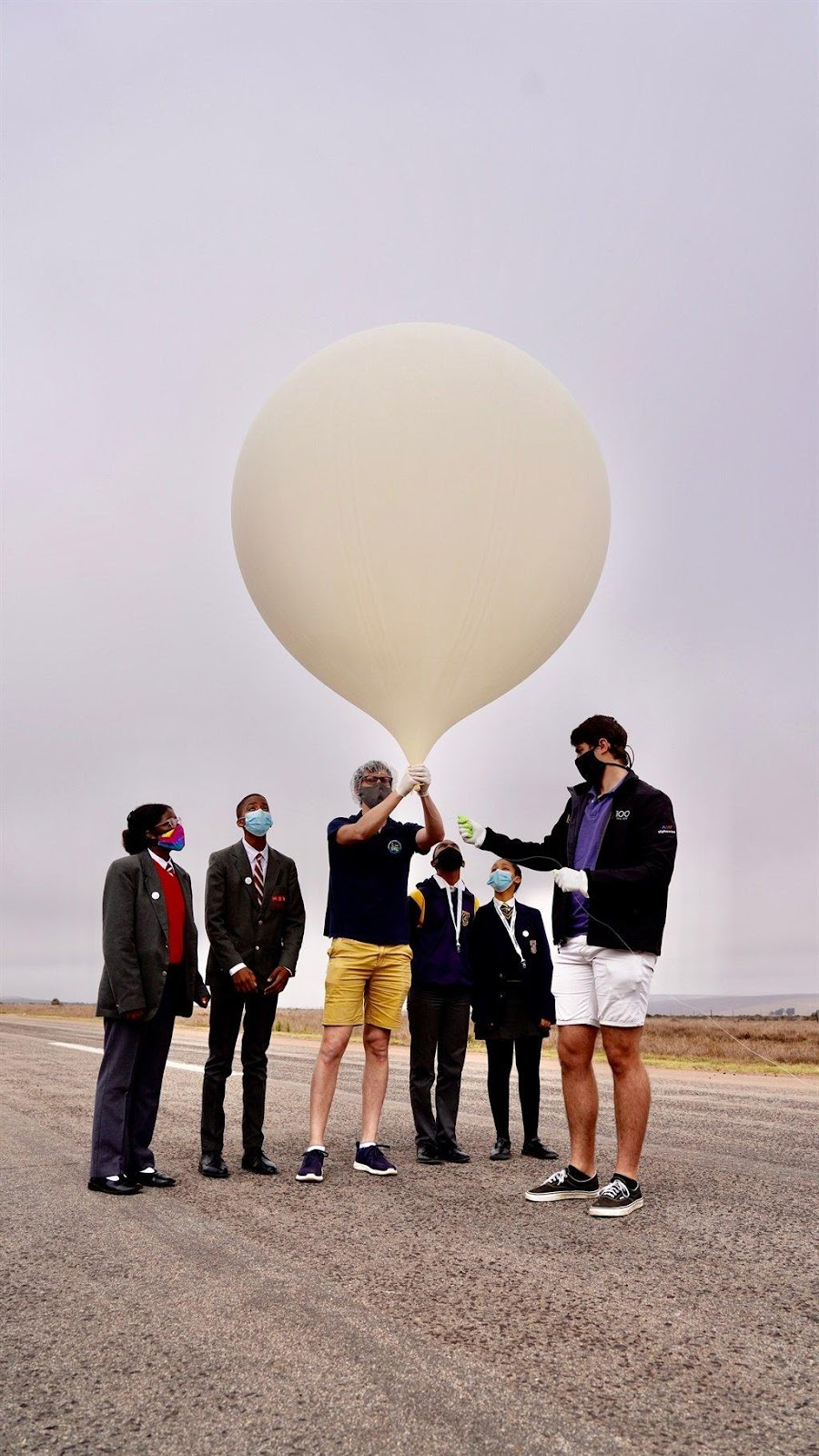 A group of people holding a balloon  Description automatically generated