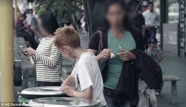 Минувачи се разминуваат со бездомно дете на улица кое бара храна во канта за отпадоци. Социјален експеримент организиран од полицијата во Нов Зеланд. [ИЗВОР: DAILY MAIL, Нов Зеланд] https://www.dailymail.co.uk/news/article-3502857/People-walk-past-boy-rummaging-bin-NZ-Police-recruitment-campaign.html