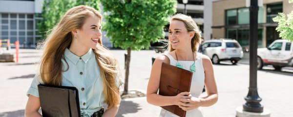 Two female students smiling and walking to class holding notebooks