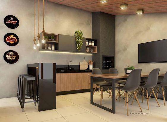 Area gourmet em estilo moderno com churrasqueira revestida de cimento queimado, com armários e bancada em madeira, cadeiras pretas, teto revestido de madeira, piso de cerâmica branca, quadros decorativos, TV e lâmpadas pendentes.