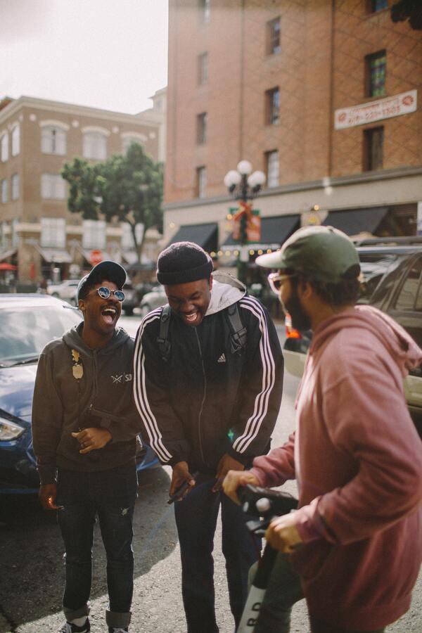 três amigos rindo na rua