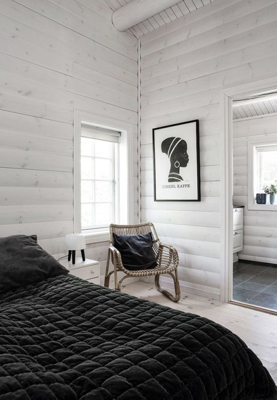 white painted cabin bedroom: black bedding and throw pillow with black and white canvas and table lamp