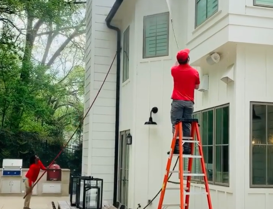 Two men pressure washing the outside of a house