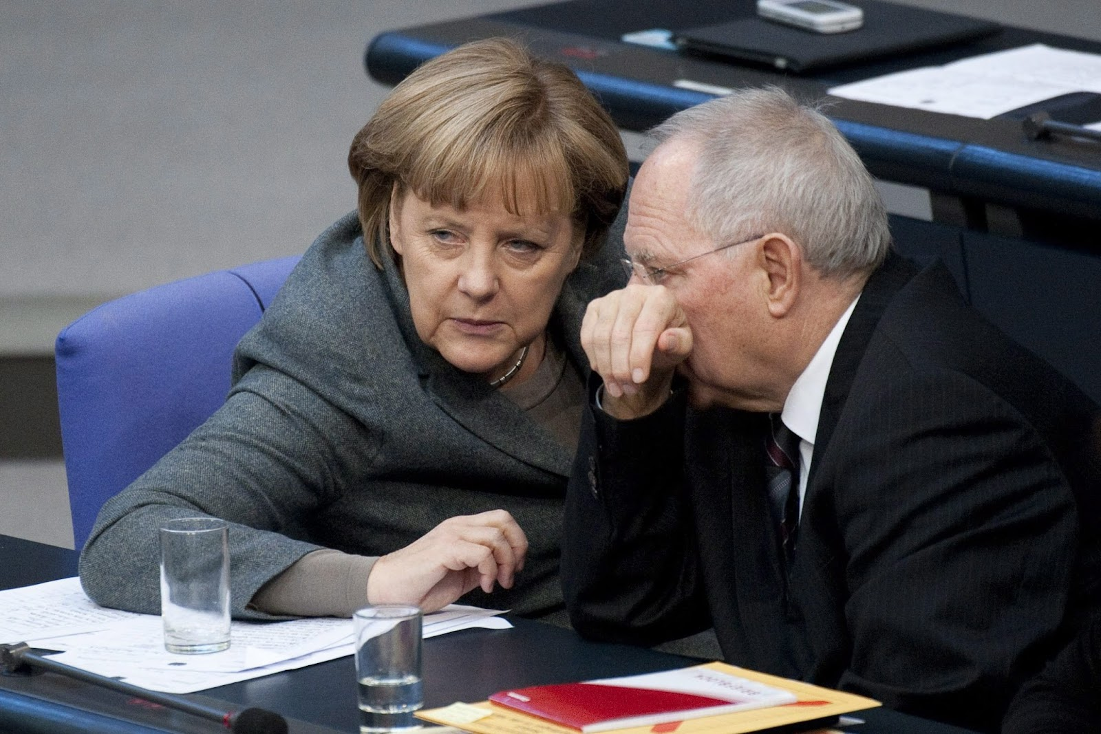 epa03014771 German Chancellor Angela Merkel and german Finance Minister Wolfgang Schaeuble chat at the Bundestag in Berlin, Germany, 25 November 2011. Reports state that the German Federal Government votes on the German 2012 budget, 25 November 2011.  EPA/ROBERT SCHLESINGER