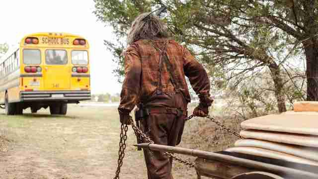 Still from Lumberjack Man (2015). A long haired figure dressed in a dirty plaid shirt is facing away from the camera as he pulls a cart with thick chains. He is following a yellow schoolbus along a dirt path.