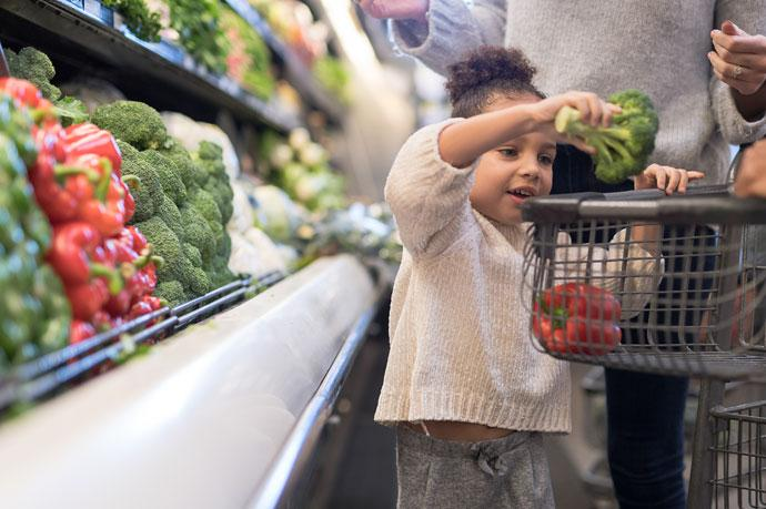 A young child places broccoli into a shopping trolley