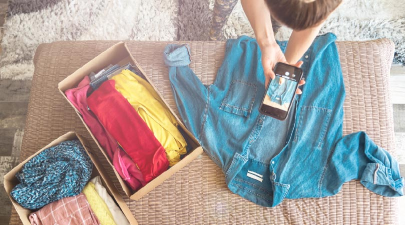 A woman taking pictures of her old clothes to sell online