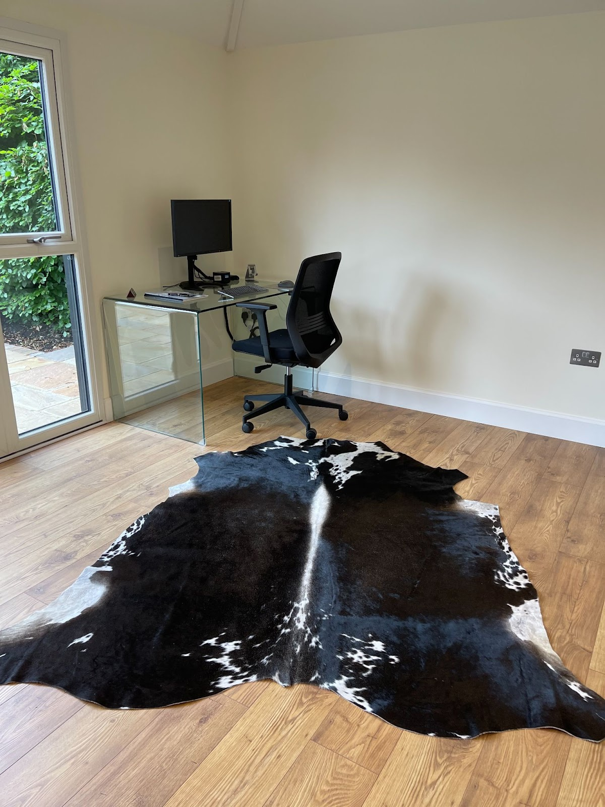 Black and White cowhide rug in home office space next to desk