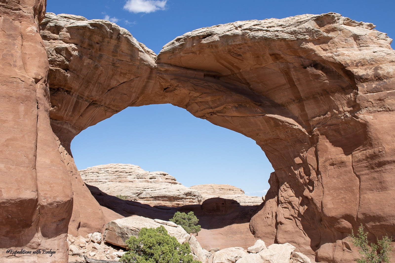 A sandstone arch creates a window to more sandstone rocks behind it.  Greenery dots the foreground.