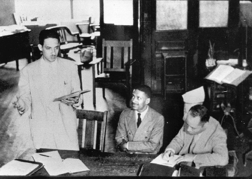 A black-and-white photograph depicting Thurgood Marshall giving a court address while Donald Gaines Murray and Charles Houston look on.