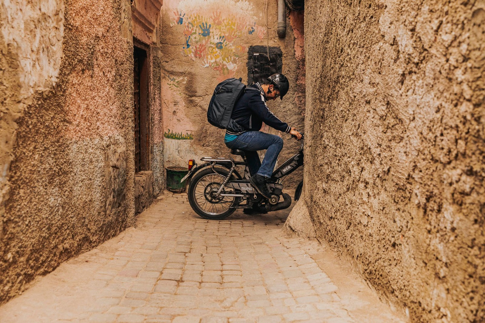 A man on a scooter in a rustic alleyway.
