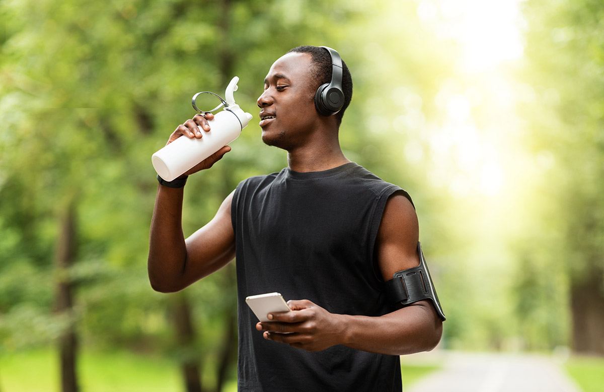 Athletic man wearing headphones and holding a water bottle