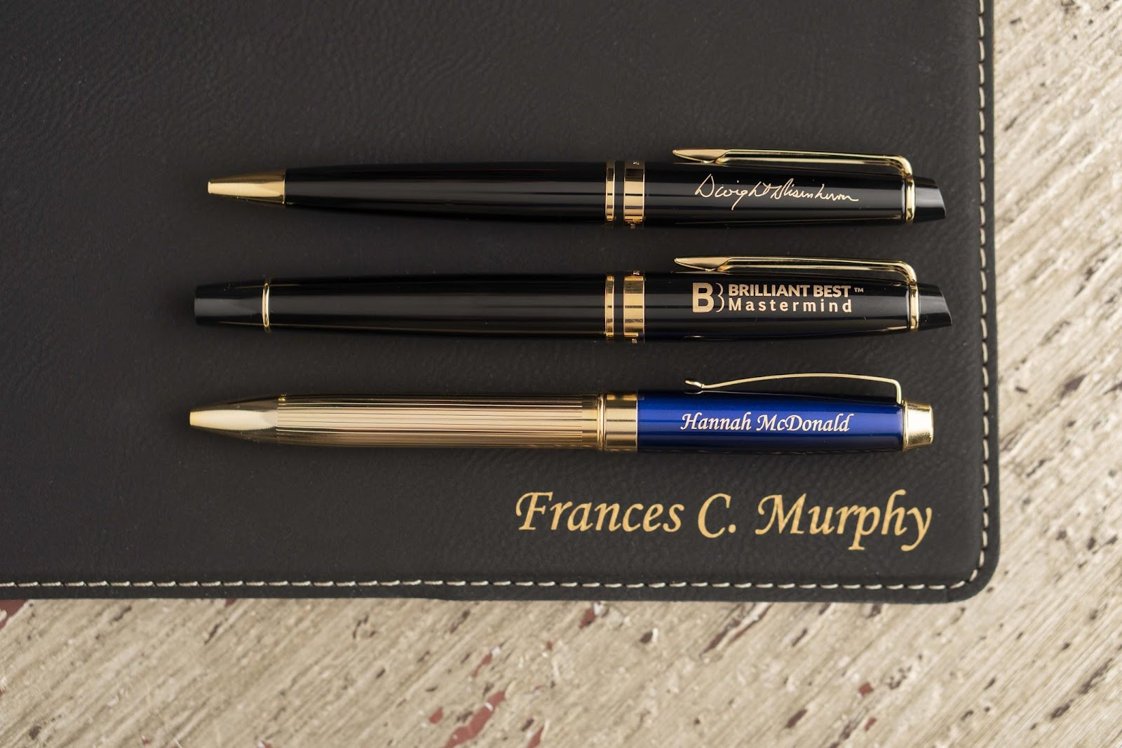Two Waterman Expert pens—one with signature engraving, the other with a promotional logo engraving—rest on a custom engraved padfolio
