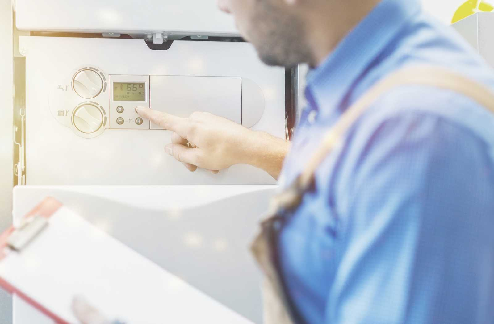 Technician adjusting the settings on a water heater