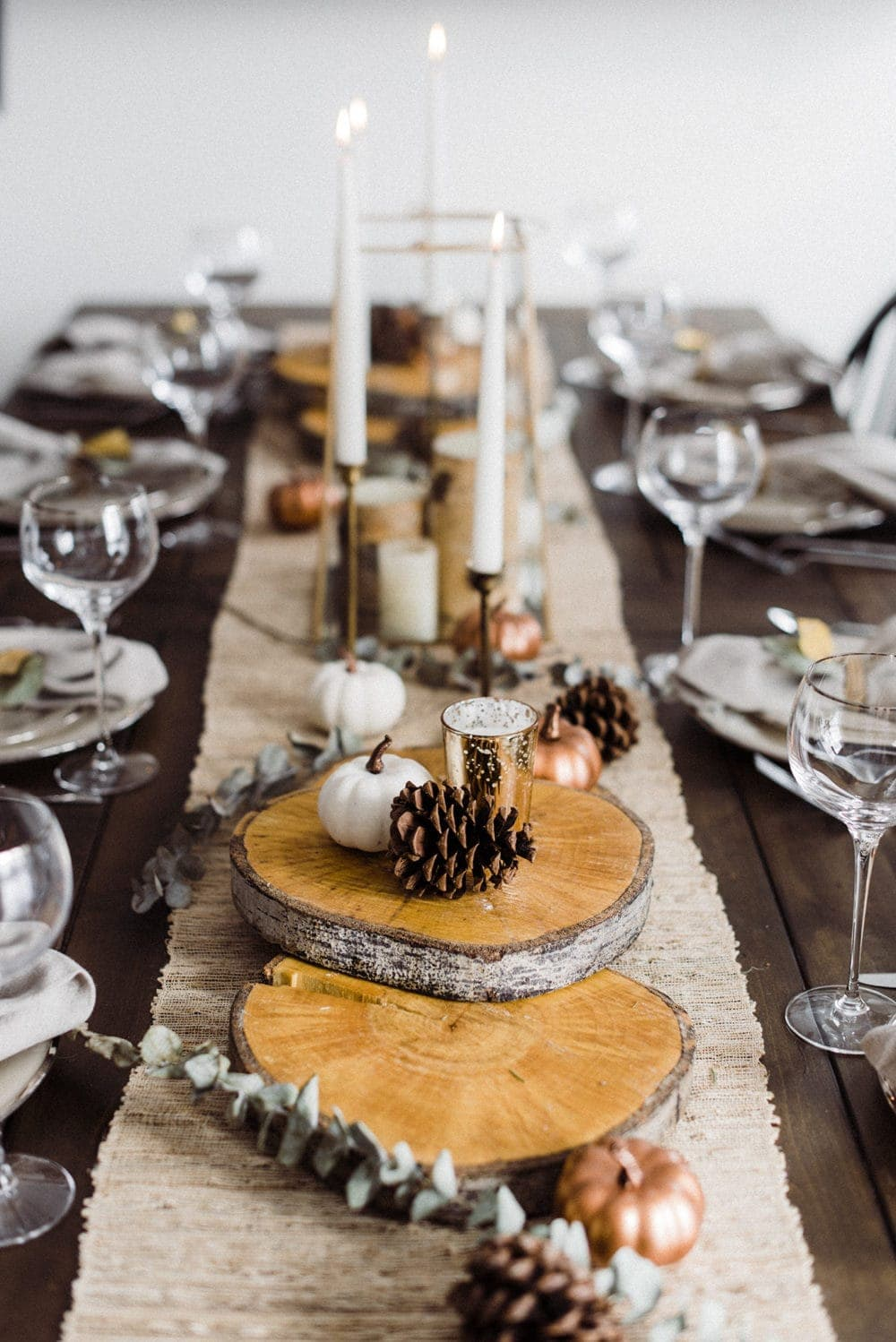 modern fall tablescape decor with pine cones, white pumpkins, candles, glass dishware, wooden table and faux plants