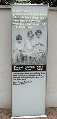 Stele, darauf drei Kinder abgebildet und Text: »Anne Frank, geboren am 12. Juni 1929, lebte mit ihren Eltern und ihrer älteren Schester Margot bis zum März 1931 in diesem Haus...«.