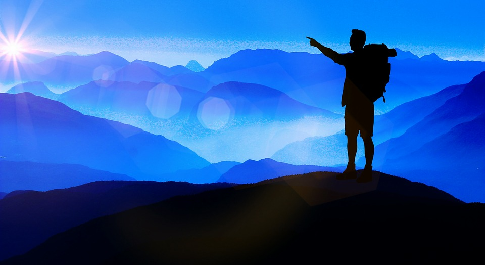 man standing with blue mountains in background