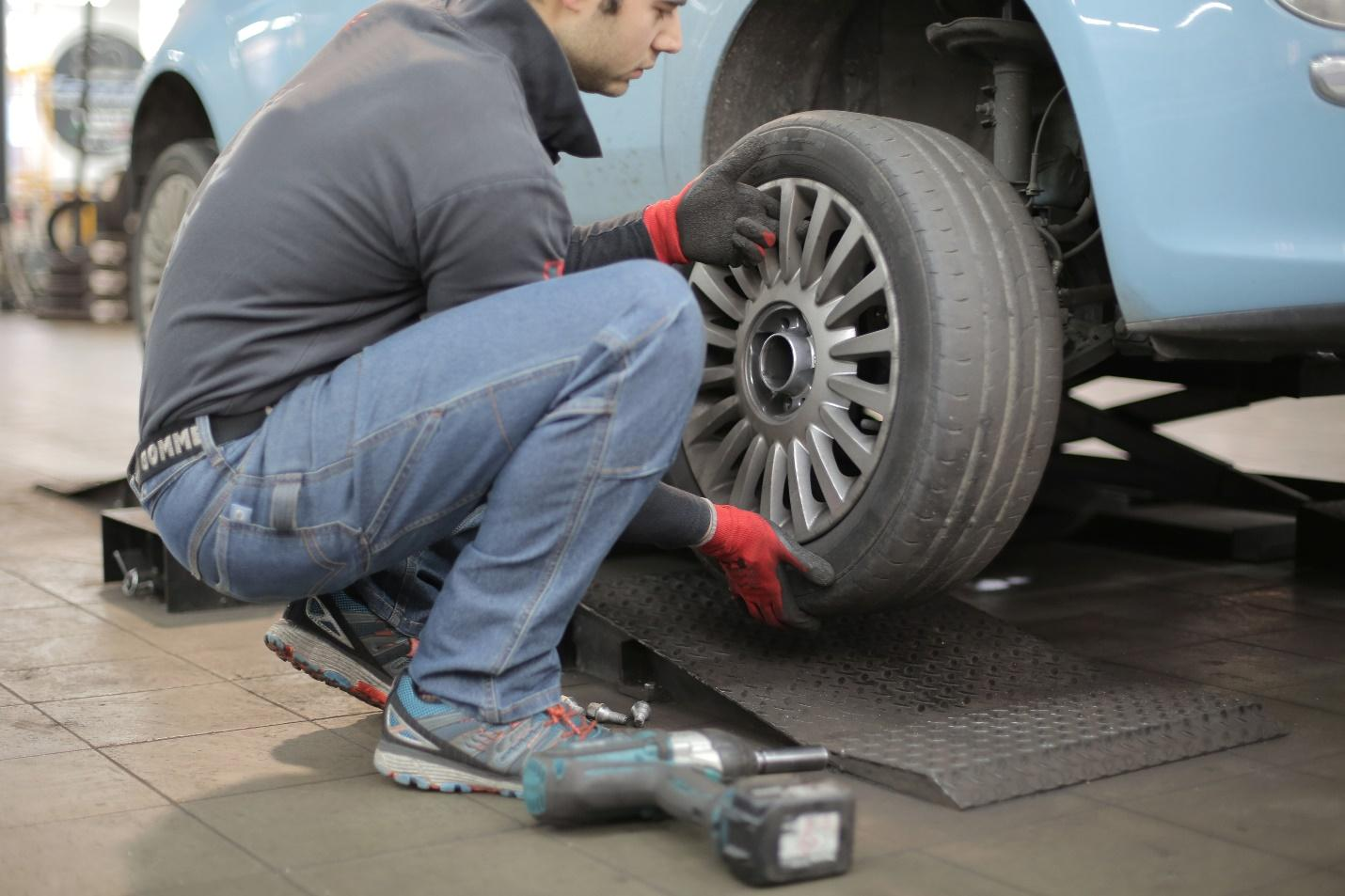 A person working on a car tire  Description automatically generated with low confidence