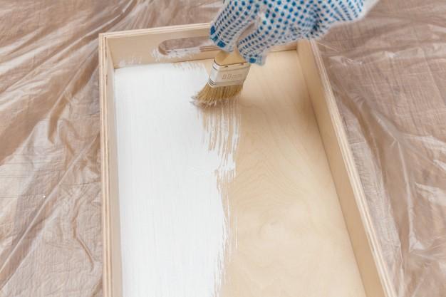 Pintando uma bandeja de madeira com tinta branca Foto Premium