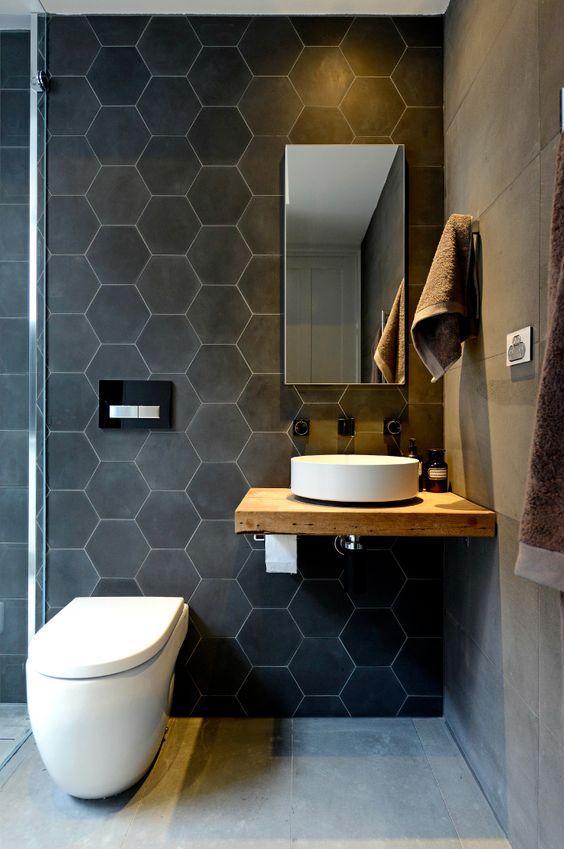 Banheiro com revestimento hexagonal preto na parede, bancada da pia de madeira com cuba branca, parede lateral e piso imitando cimento queimado