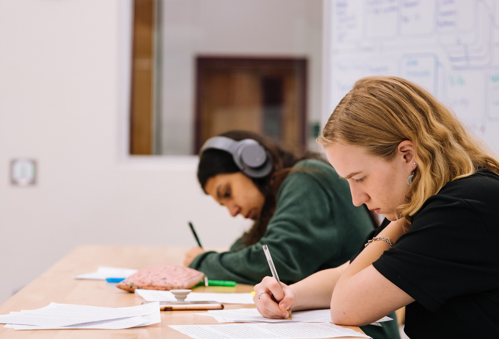 Two students sit at a table in a classroom writing on papers. A whiteboard in the background has some notes on it. One student is wearing headphones and neither are talking. Both look like they are in deep concentration.