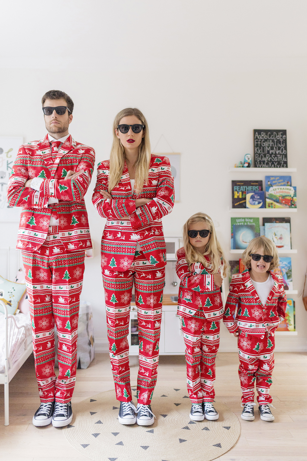 fun christmas card pose of family in matching holiday suits and sunglasses