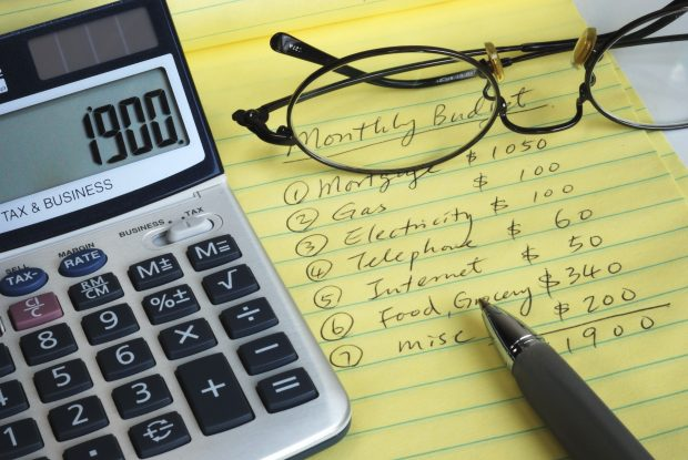 Image of a calculator, glasses, a pen and a notepad with expenses written on it - represent that you should learn the truth about budget and stop taking notes of every single dollar you spend