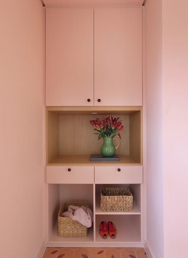 Hall com predes rosas, armário rosa e piso em tom rose