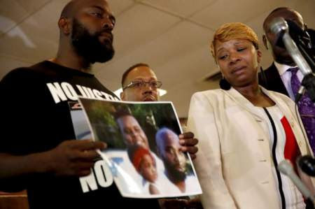 Lesley McSpadden (right), mother of 18-year-old Michael Brown, watches as Brown's father, Michael Brown Sr., holds a family picture, during a news conference, Aug. 11, 2014.