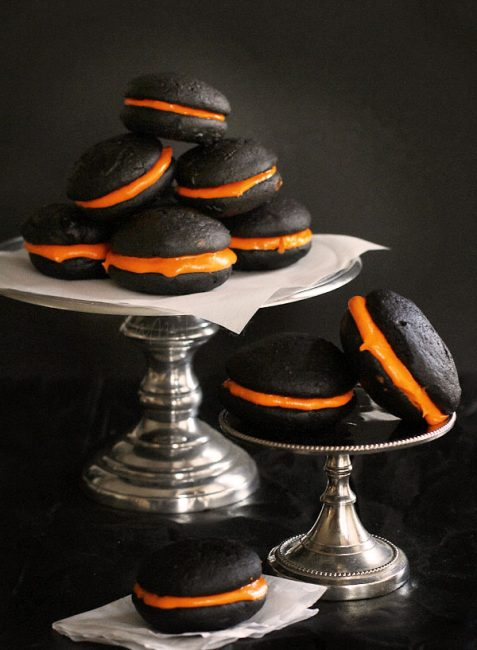 Photo of stacks of black velvet whoopie pies with bright orange filling.