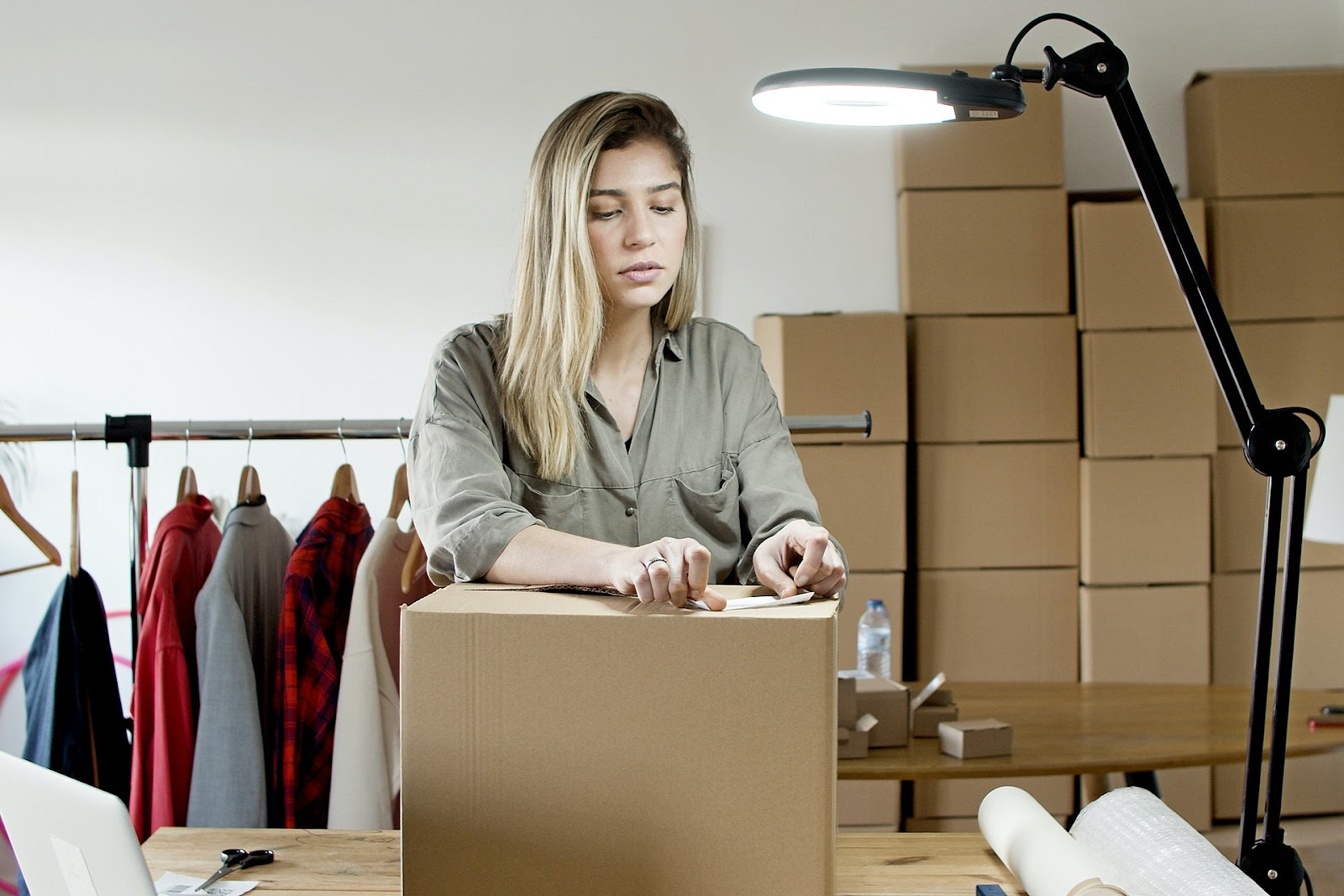 Woman labelling a box to send out products sold from an online store.