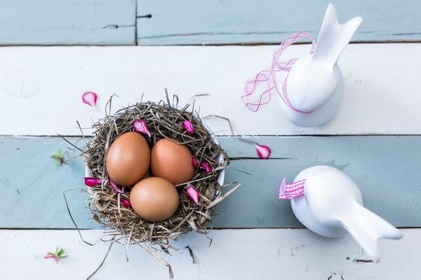 Uma cesta com três ovos marrons ao lado de dois coelhos de porcelana