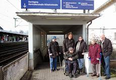 Menschen mit Gehhilfen oder im Rollstuhl vor der Treppe des Gerresheimer Bahnhofs.