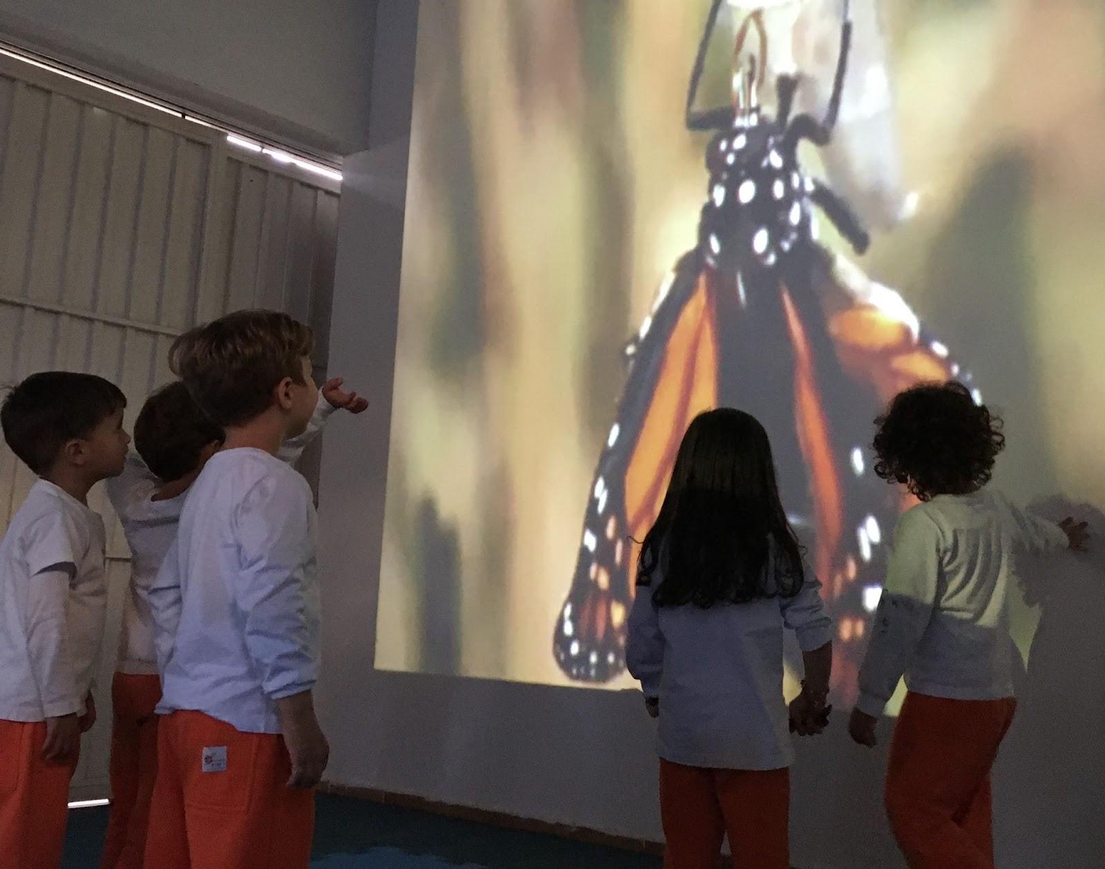 A imagem mostra um grupo de crianças de camisetas brancas e calças de cor de laranja observando uma imagem. A imagem projetada mostra uma borboleta de asas cor de laranja, preto e pintas brancas.