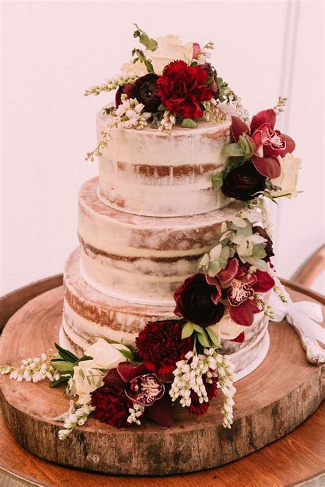 Three tier naked wedding cake decorated with burgundy