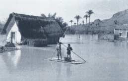 Dos niños con pértigas sobre una balsa, en un caserío anegado