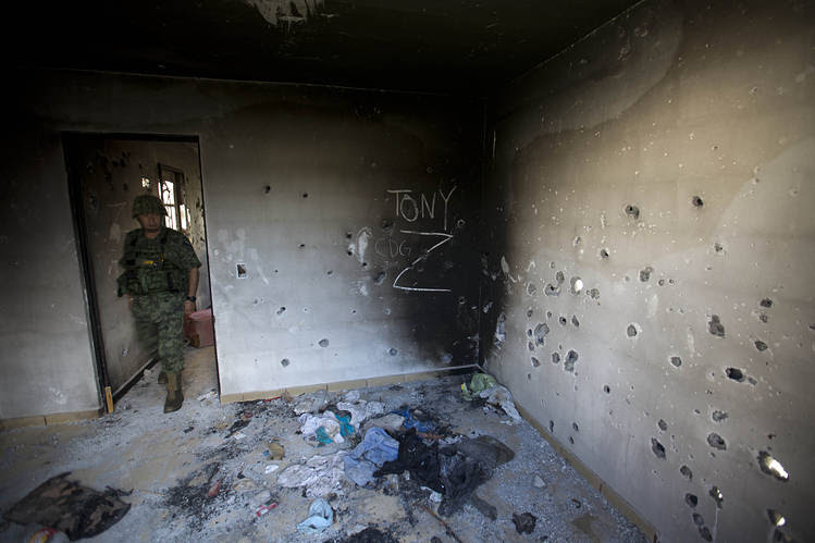 A soldier entered a bullet-riddled home covered with the initials of drug cartels—CDG for the Gulf Cartel and Z for Los Zetas—in Ciudad Victoria, Mexico, Sept. 6, 2014.