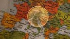 Euro coin superimposed over a map of Europe