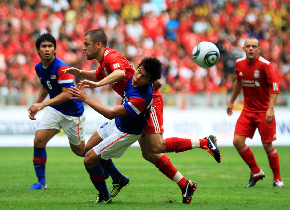 Joe Cole of Liverpool clashes with Mohd Muslim Ahmad of Malaysia during the pre-season friendly match between Malaysia and Liverpool at the Bukit Jalil National Stadium on July 16, 2011 in Kuala Lumpur, Malaysia.