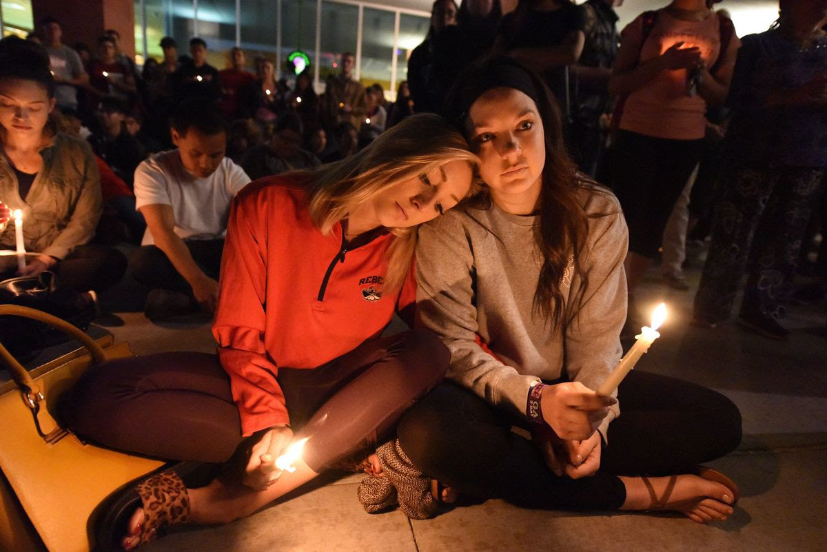 Lindsay Cotterman (L) and Shawna Pieruschka attend a candlelight vigil at the University of Las Vegas student union October 2, 2017, after a gunman killed at least 58 people and wounded more than 500 others when he opened fire on a country music concert in Las Vegas, Nevada late October 1, 2017.  / AFP PHOTO / Robyn Beck        (Photo credit should read ROBYN BECK/AFP/Getty Images)