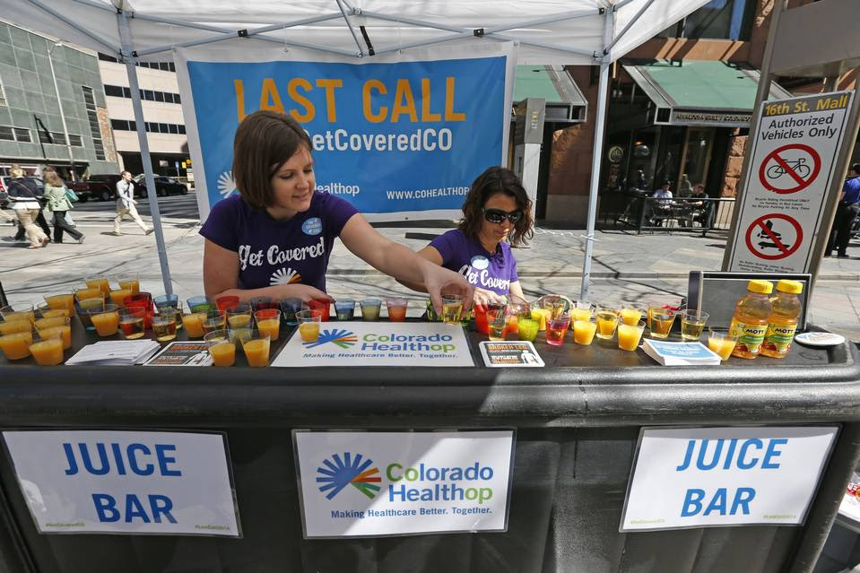 Colorado HealthOP, a health care co-op, is closing, forcing about  80,000 Coloradans to find a new insurer. Last year, in file photo above, literature and shots of juice were handed out at a pedestrian mall during a promotional campaign launched by the co-op.