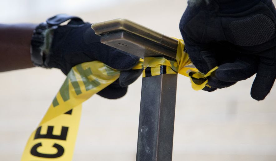 A police officer ties police tape to a handrail. (Associated Press) **FILE**