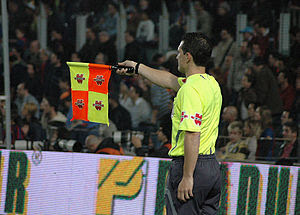 A Spanish linesman signalling an off-side offe...
