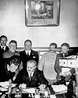 Молотов подписва пакта за ненападение между Германия и СССР. На заден план са Рибентроп и Сталин.