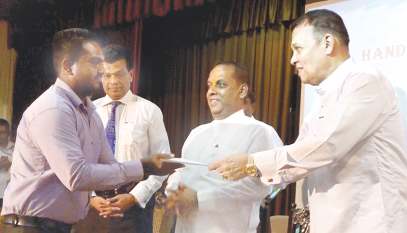 Minister Mahinda Samarasinghe handing over an appointment for an employee.
