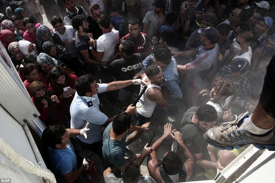 Pushing:A policeman hits a migrant as police try to disperse hundreds of migrants during a registration procedure in Kos town today