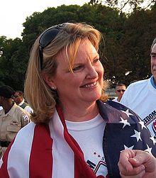 Debra Burlingame wraps herself in the flag.jpg