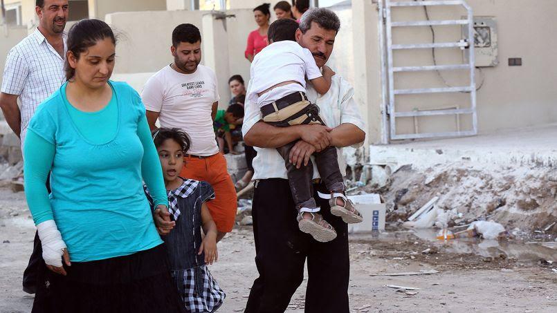 Des déplacés chrétiens arpentent les rues de Qaraqosh où ils se sont réfugiés pour fuir les violences de Mossoul.