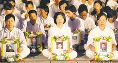 Falun Gong practitioners hold portraits of victims of China's crackdown during a vigil in Taiwan.